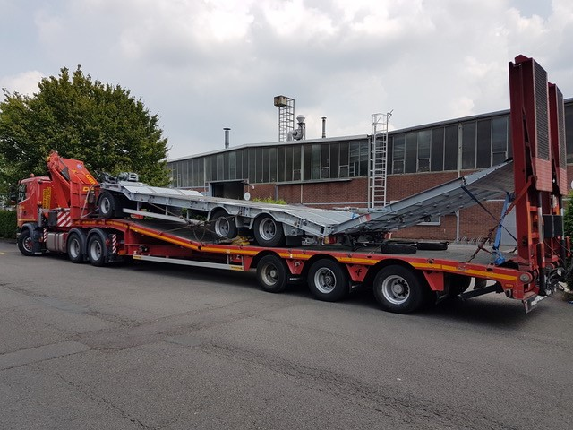 Transport avec semi-remoque surbaissée équipée avec double rampes de chargement d'une remorque